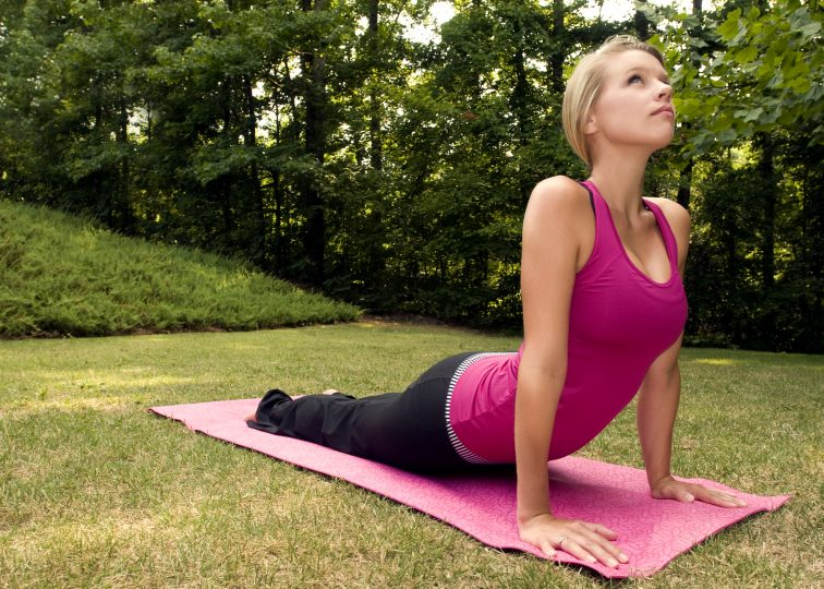 Woman doing yoga outdoors to build strength and flexibility