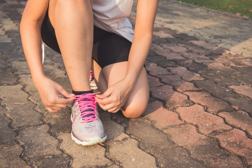 Woman tying running shoes before starting to run