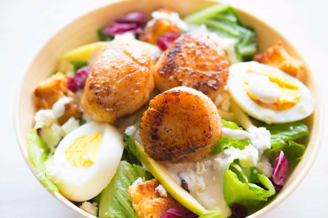 seared scallops and boiled eggs on green salad for a healthy fast lunch