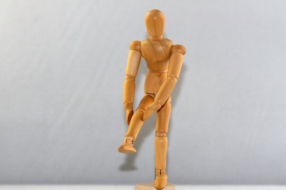 model of person holding knee in pain from an injury
