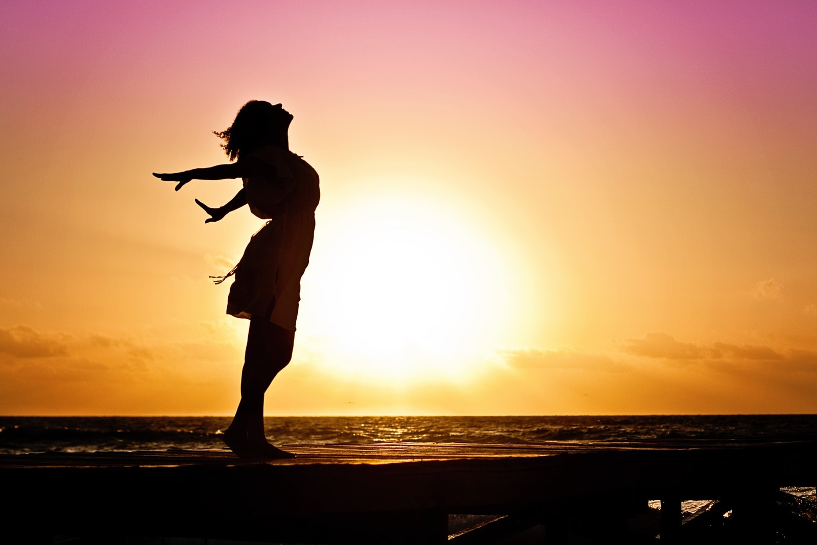 Fit and healthy middle age woman standing on beach at sunset with chest up and arms back