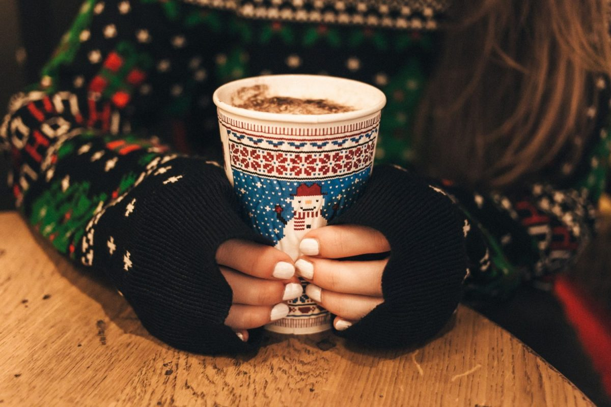 Woman in christmas sweater enjoying a cup of hot cocoa at a table