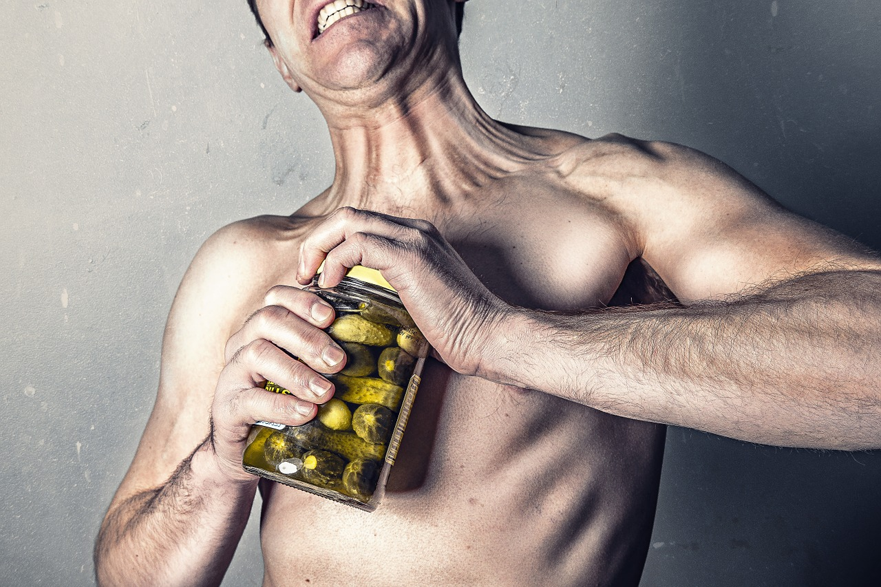 Lean middle age man trying to open a jar