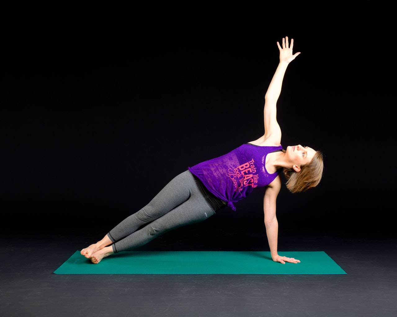Fit and healthy middle age woman in leggings and a tank top doing a plank exercise to develop core strength