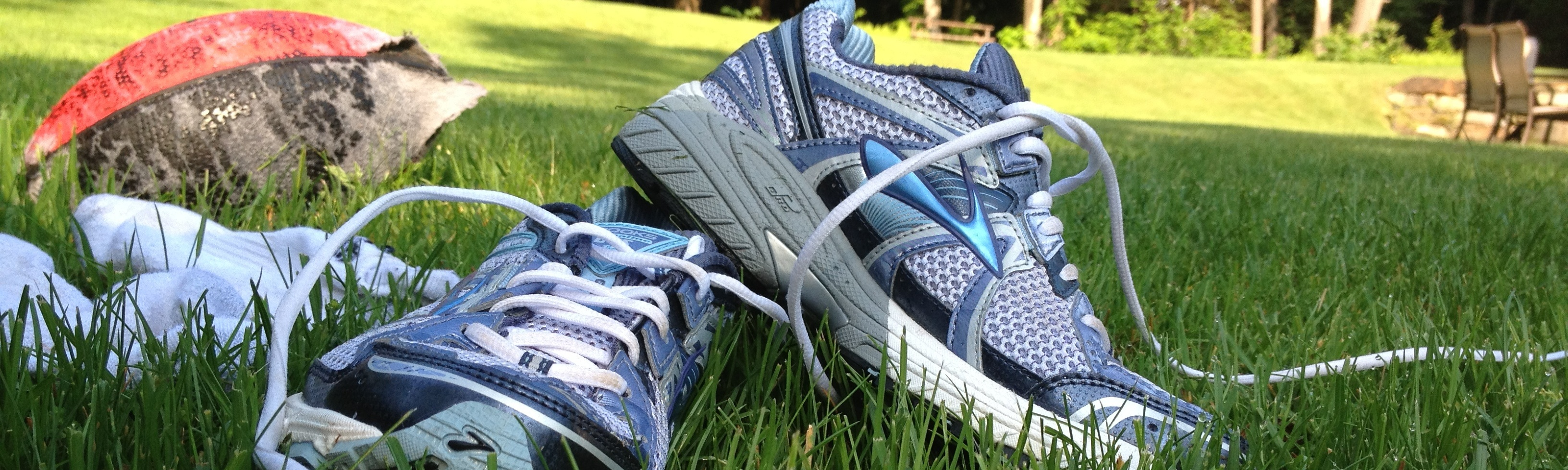 blue and white running shoes and rugby ball in a park